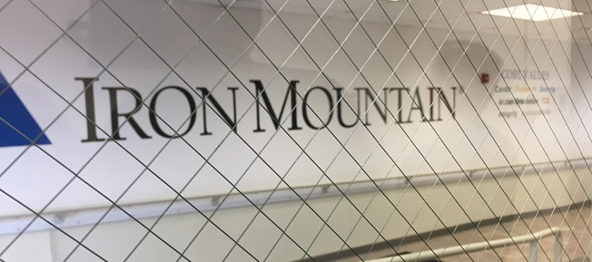 Iron Mountan printed along a hallway wall, seen through a glass door.