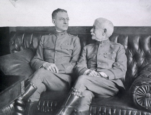 Photograph of two men in uniform sitting on a couch.
