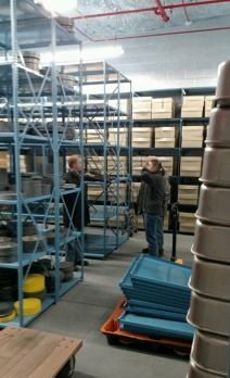A woman and man in heavy coats stand among high metal shelves of boxes.