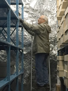 A man in a coat on a ladder looks at a box high on a metal shelf.