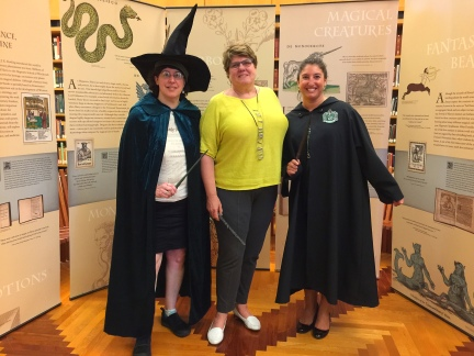 Three women standing in front of the Harry Potter banner.