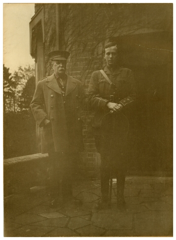 A photgraph of an older man with a young man in uniform.