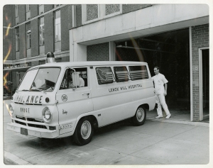 An ambulance van just outside a garage in a large building.