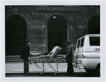 Two men with a patient on a stretcher next to an ambulance van in front of a stone building.