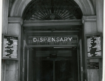 An ornate arched entrance labeled dispensary with additioanl wayfinding signs.