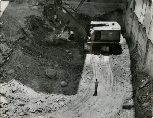 A man stands in a deep excavation next to a large excavator machine.