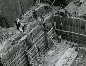 Men work installing foundation walls for a large building.