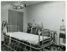 A hospital bed in a tiled room with medical equippment.