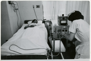 A patient lays in a bed while a nurse adjust a medical instrument.
