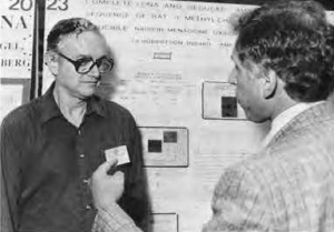 Two men talk in front of a scientific poster.
