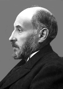 A photographic portrait in profile, of a middle aged man in a full beard.