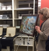 A painting of Smokey on an easel in a collections storage area.