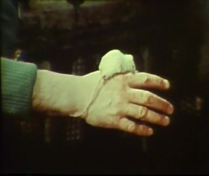 A small white mouse sits on a man's hand.