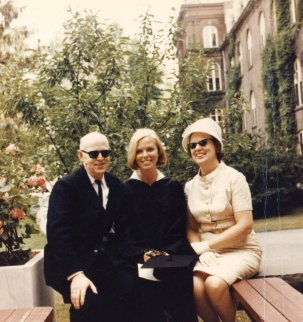 Photograph of three people sitting - a man in a suit with sunglasses on the left, a women with a graduation gown in the center, and a woman in a light-colored dress with sunglasses and a hat on the right.