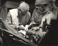 Close up of 3 surgeons performing open heart surgery.