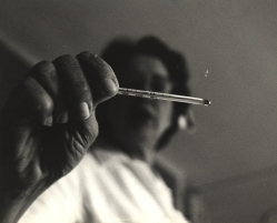 Close up of a nurse reading a thermometer.