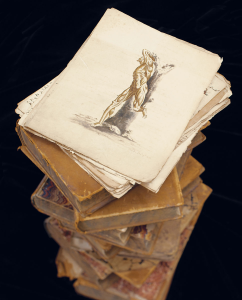 Photograph of a stack of papers containing illustrations on top of several books.