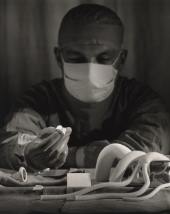 A surgeon wearing his mask sits at table, examining various artificial valves.