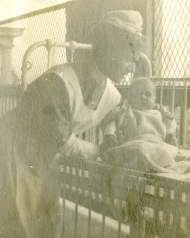 Cornelia Mercer leans over a crib to adjust the position of an infant patient
