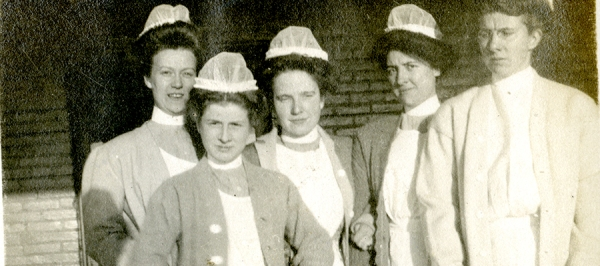 Cornelia Mercer with four fellow nurses, all posing for the camera in white uniforms