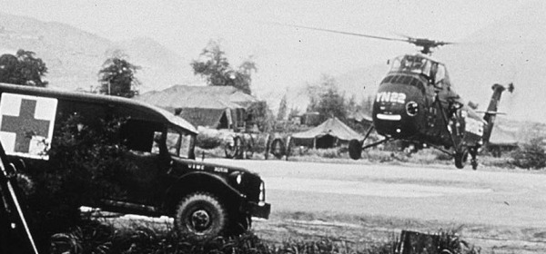 An ambulance marked with a red cross waits by an open field where a helicopter is landing.