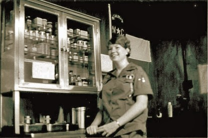 A Woman In Uniform By Cabinet Of Medical Supplies