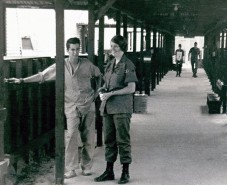 A woman in uniform and a man in scrubs stand in a long shed like building.