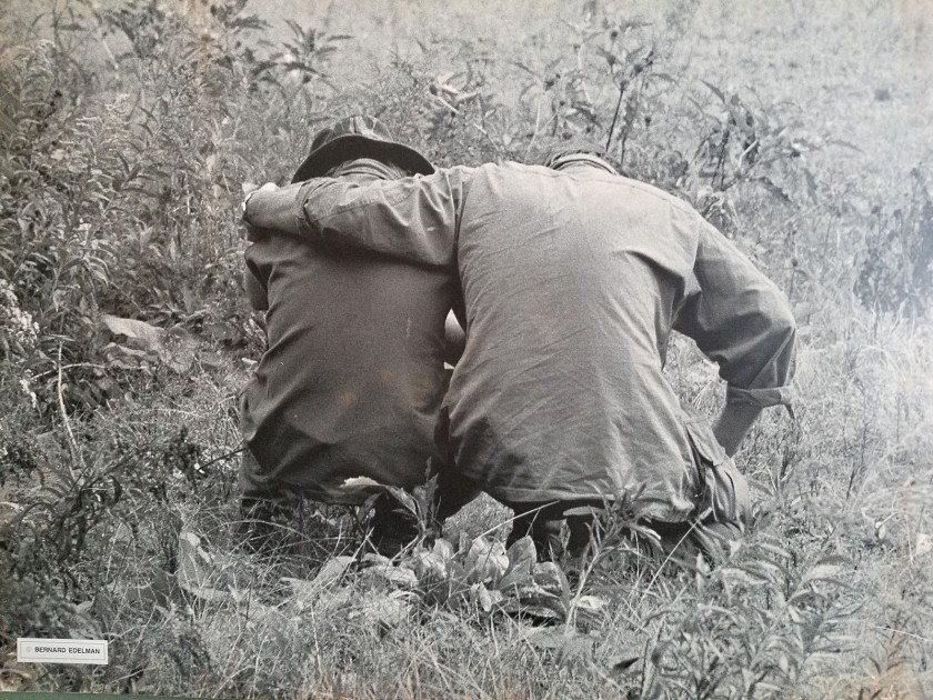 Two people in uniform sit in a field wither their backs to the camera, one has his arm around the other's shoulder.