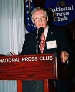 An older man speaks at a podium in front of an american flag.
