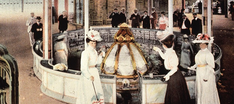 Shows people standing at the fountain, La Grande Grille, in Vichy, France, and drinking the water.