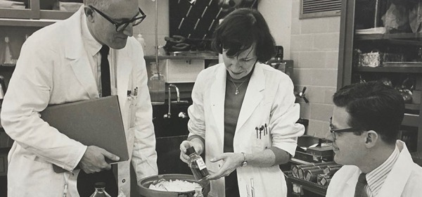 A woman and two men work in a laboratory.