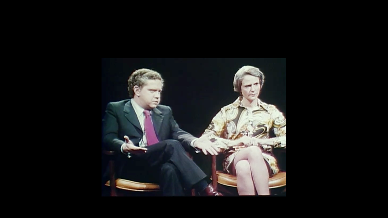 A man and woman sit next to each other in a formal interview like setting.