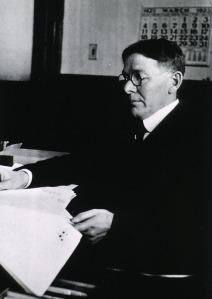 A man in a suit wearing glasses sits at a desk looking at papers.