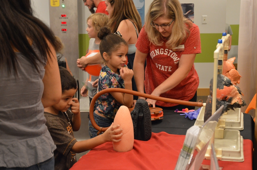 Kids and adults work at an activity station
