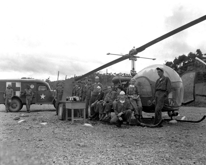 Military personnel pose with a helicopter, ambulance, and medical equippment.
