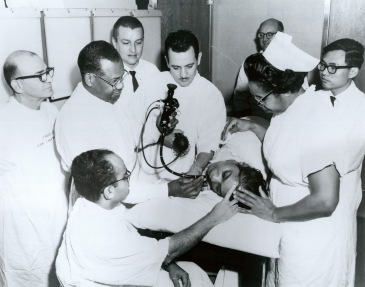 In an exam room, a male, African American doctor performs gastroscopy on an African American woman while others look on