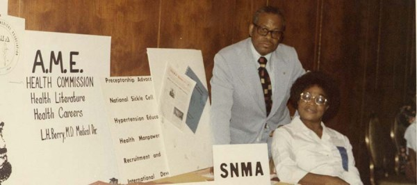 An African American man and woman next to posters at a conference