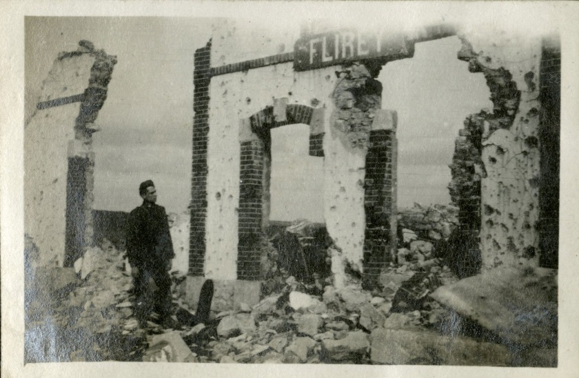 A man stands in the shell of a destroyed brick building.