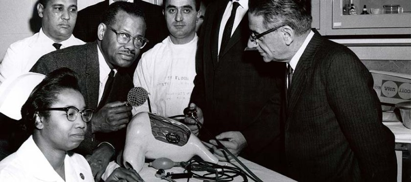 An African American man demonstrates a medical model to a group