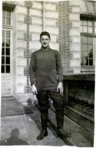A young man stands on a balcony of a large building.