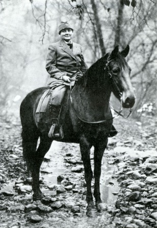 Photograph of a woman in uniform on a horse in a rural setting.