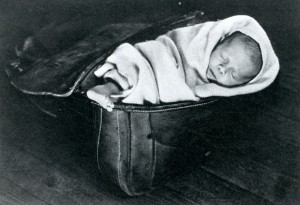 A baby wrapped in a blanket in a saddlebag.