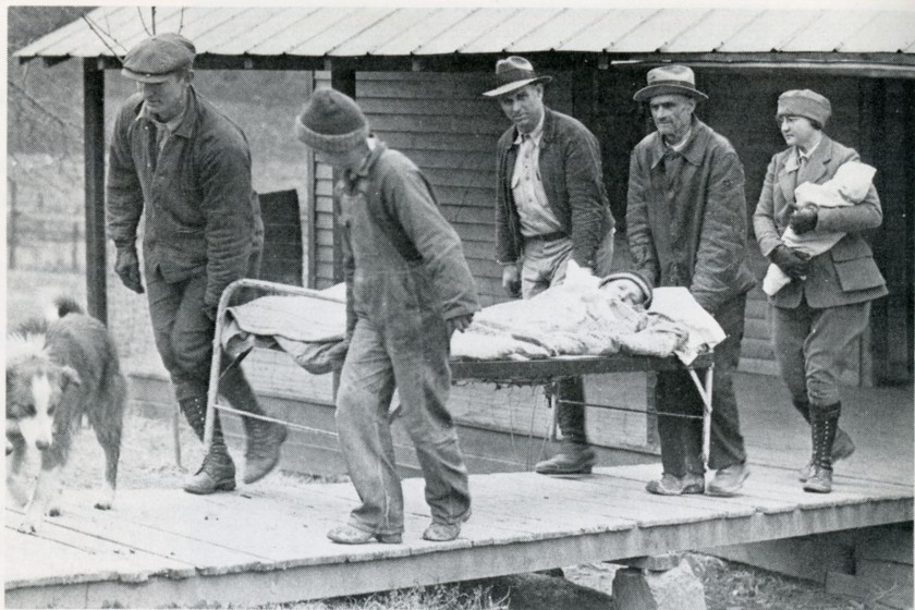 Four men carry a child on a metal frame bed out of a building, a nurse carrying a baby follows.