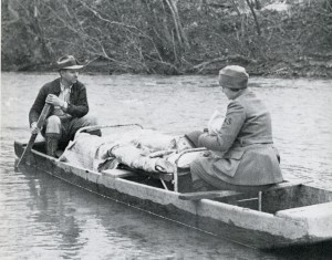 A woman in a nurse uniform holding a baby sits in a small flat wooden boat with a boy on a bed while a man rows.