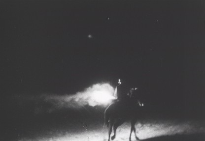 Avery dark scene of a rider on a horse carrying a flaming torch.