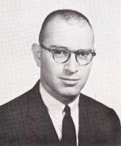 Portrait of a man in a suit and glasses.