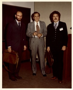 A casual photograph of a group of three men in suits.