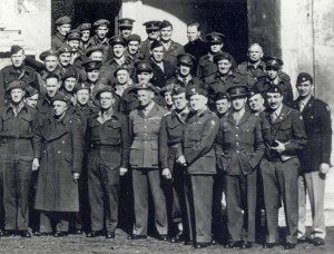 A group of men in uniform pose outdoors for a group photograph.