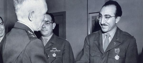 DeBakey, in uniform, shaking hands with an older man.
