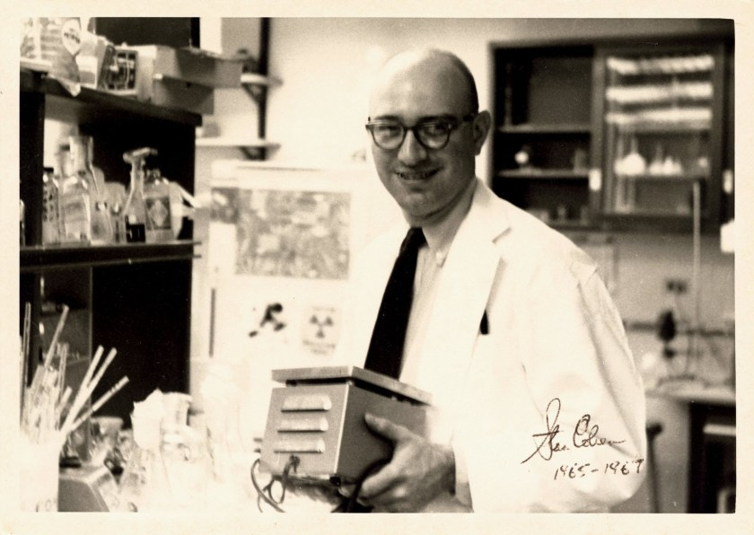 A candid photograph of Stan Cohen in a white coat, in a laboratory holding a piece of equippment.